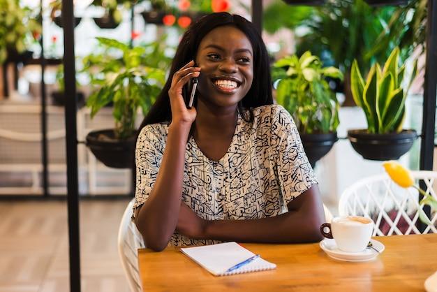 Portret miłej młodej kobiety siedzącej w kawiarni na świeżym powietrzu, rozmawiając przez telefon komórkowy