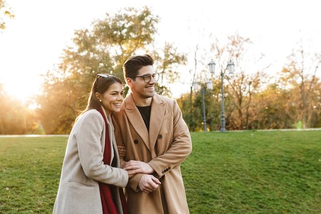 Portret miłej pary dorywczo mężczyzny i kobiety w wieku 20 lat uśmiechających się i przytulających się podczas spaceru w jesiennym parku