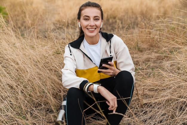 Portret miłej, radosnej kobiety w stroju sportowym, korzystającej ze słuchawek i smartfona, siedząc na suchej trawie