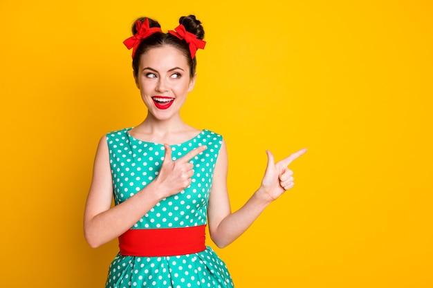 Portret miłej, uroczej, wesołej dziewczyny, wskazując palcem wskazującym na bok, kopiując pustą przestrzeń odizolowaną nad żywym żółtym kolorem tła