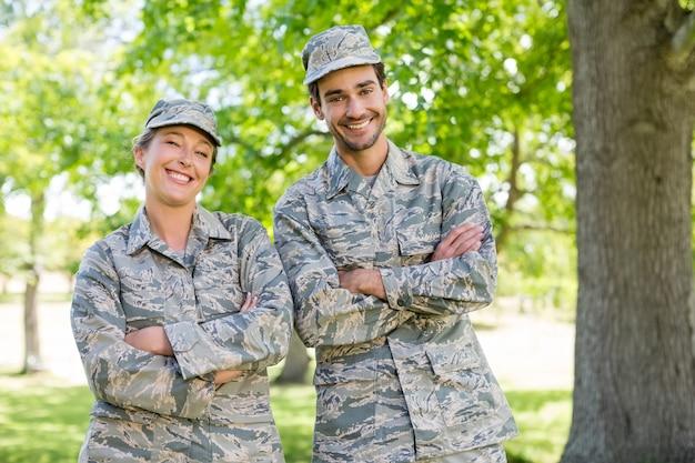 Portret militarna pary pozycja z rękami krzyżował w parku