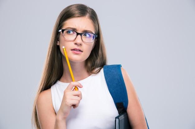 Portret miło nastolatka kobiet trzymając ołówek na białym tle. odwracając wzrok