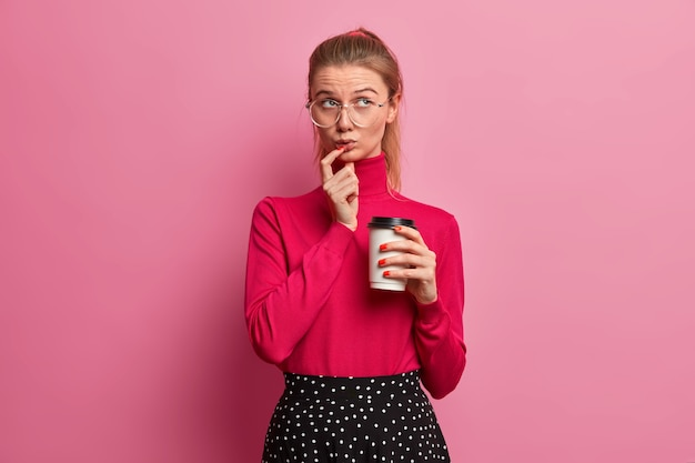 Portret miło piękna nastoletnia europejska dziewczyna skoncentrowana powyżej trzyma jednorazową filiżankę kawy