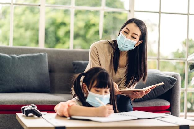 Portret miłość azjatycka matka rodziny i mała azjatycka dziewczynka ucząca się i pisząca w książce ołówkiem, odrabiająca pracę domową w kwarantannie dla koronawirusa w masce ochronnej z dystansem społecznym w domu