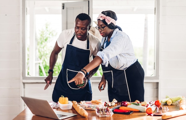 Portret miłości afroamerykanin para dobrze się bawi, gotując razem i szuka przepisu w internecie z laptopem, aby przygotować pyszne jedzenie w kuchni w domu