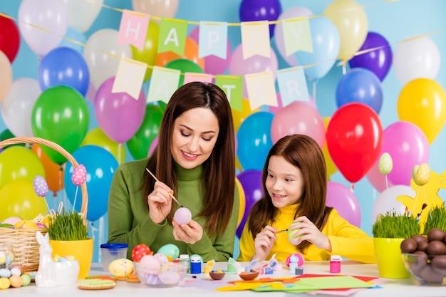 Portret miłych, atrakcyjnych, kreatywnych, wesołych, wesołych sióstr dziewcząt malujących jajka, tworzących rękodzieło, przygotowujących się do kwietnia niestandardowe małe dziecko siostra