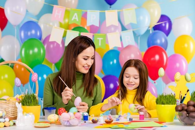 Portret miłych, atrakcyjnych, uroczych wesołych, wesołych dziewcząt malujących jajka, tworzących dzieła sztuki spędzające czas z siostrami, małe małe potomstwo