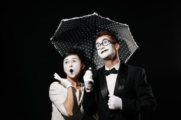 Portret mima zaskoczona para z parasolem na czarnym tle. mężczyzna w smokingu i okularach i kobieta w białej sukni