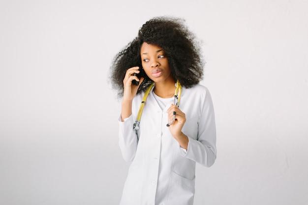 Portret młoda afrykanin lekarka w mundurze z stetoskopem w szpitalu na białym tle i opowiadać przez telefon