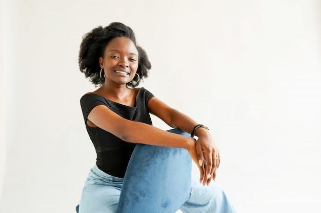 Portret młoda amerykanin afrykańskiego pochodzenia kobieta odizolowywająca nad bielem