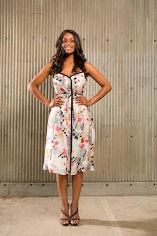 Portret młoda amerykanin afrykańskiego pochodzenia pozycja przed betonową ścianą i ono uśmiecha się przy kamerą