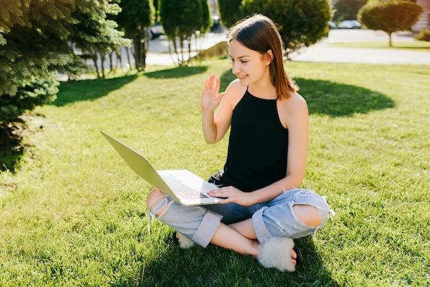 Portret młoda atrakcyjna dziewczyna komunikuje się online rozmową wideo, ma skype rozmowę z przyjaciółmi, używa laptop podczas gdy siedzący na trawie w parku.