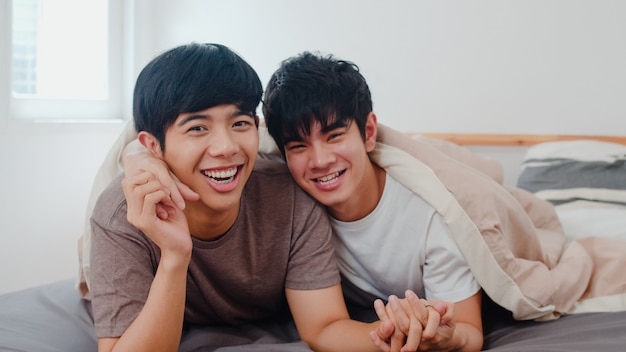 Portret młoda azjatycka homoseksualna para czuje się szczęśliwy w domu. asia lgbtq + mężczyźni relaksują się zębami i patrzą w kamerę, a reszta spędza romantyczny czas po przebudzeniu w sypialni w nowoczesnym domu rano.
