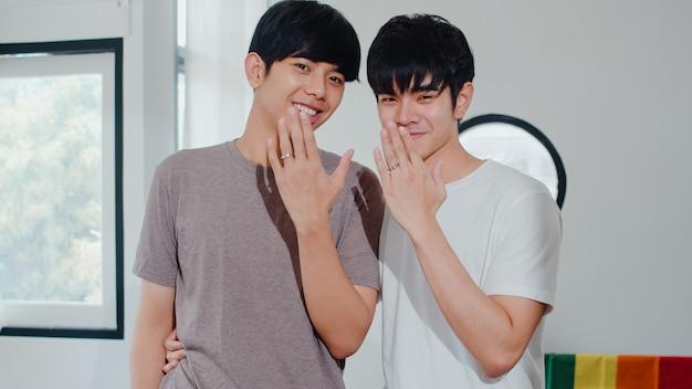 Portret młoda azjatycka homoseksualna para czuje szczęśliwego seansu pierścionek w domu. asia lgbtq + mężczyźni relaksują się zębami, patrząc do kamery, a rano przytulają się w nowoczesnym salonie w domu.