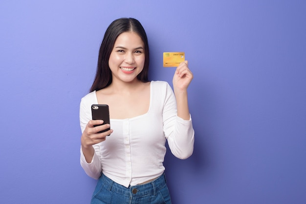 Portret młoda azjatycka kobieta używa telefon komórkowego z kredytową kartą na purpurowym tle