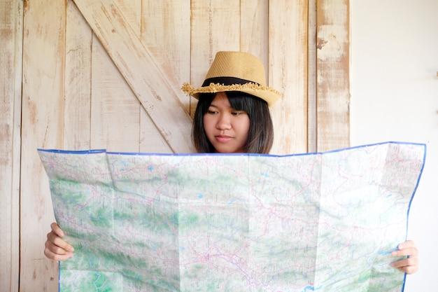 Portret młoda azjatykcia dziewczyna podróżnik trzyma mapę z uśmiechniętą twarzą, podróż wakacje letni wakacje pojęcie