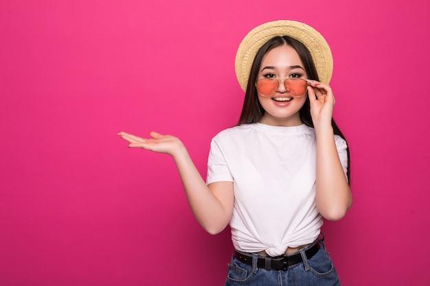 Portret młoda azjatykcia dziewczyna w okularach przeciwsłonecznych na menchii ścianie
