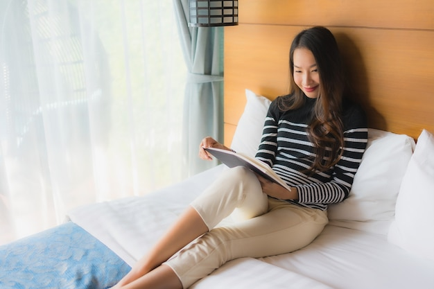 Portret młoda azjatykcia kobieta czyta książkę w sypialni