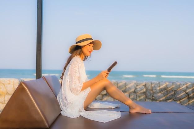 Portret młoda azjatykcia kobieta czyta książkę wokoło plażowego dennego oceanu