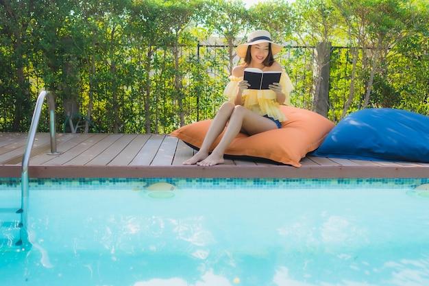 Portret młoda azjatykcia kobieta czyta książkę wokoło plenerowego pływackiego basenu