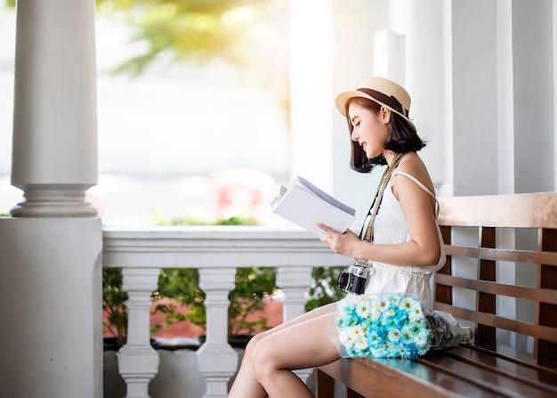 Portret młoda azjatykcia kobieta jest ubranym kapeluszową i przypadkowej odzieży czytelniczą książkę podczas gdy siedzący przy parkiem.