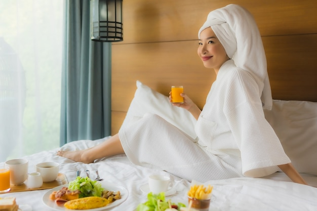 Portret młoda azjatykcia kobieta na łóżku z śniadaniem w sypialni