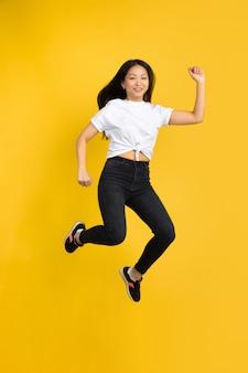 Portret młoda azjatykcia kobieta odizolowywająca na kolor żółty ścianie