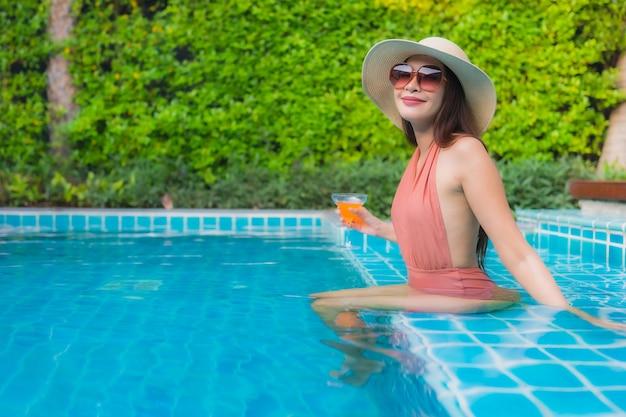 Portret młoda azjatykcia kobieta relaksuje szczęśliwego uśmiech wokoło pływackiego basenu w hotelu