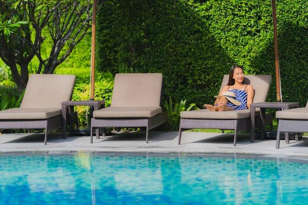 Portret młoda azjatykcia kobieta relaksuje uśmiech szczęśliwego wokoło plenerowego pływackiego basenu w hotelowym kurorcie z dennym widok na ocean