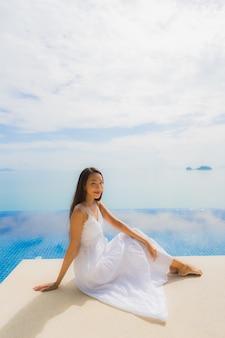 Portret młoda azjatykcia kobieta relaksuje uśmiech szczęśliwego wokoło pływackiego basenu w hotelu i kurorcie