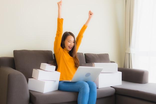 Portret młoda azjatykcia kobieta używa laptop dla pracy z pakuneczka pudełkiem