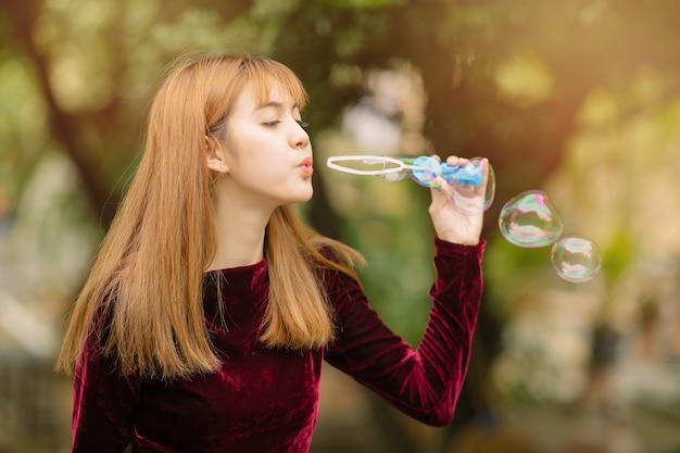 Portret młoda azjatykcia kobieta z mydlanymi balonami. młoda kobieta tworzy baniek mydlanych w parku. koncepcja szczęścia i stylu życia.