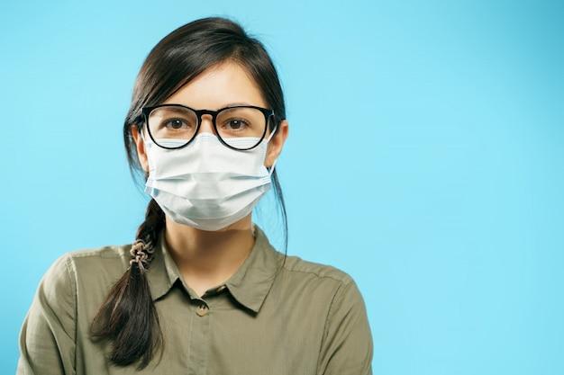 Portret młoda azjatykcia kobieta z szkłami i ochronną medyczną maską na błękitnym tle. skopiuj miejsce