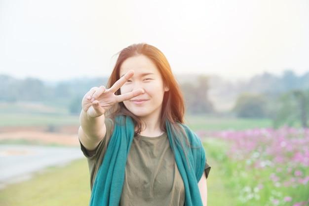 Portret młoda azjatykcia kobieta z uśmiechem i pokazywać pokoju znaka z palcami