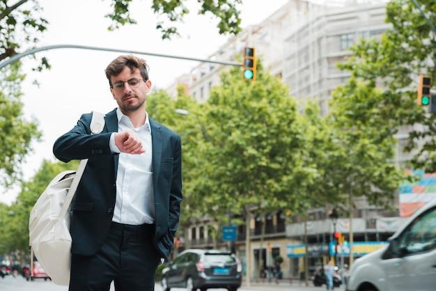 Portret młoda biznesmen pozycja na miasto ulicie sprawdza czas