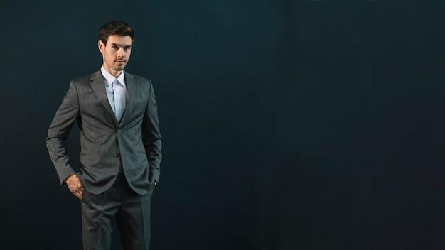 Portret młoda biznesmen pozycja przeciw ciemnemu tłu