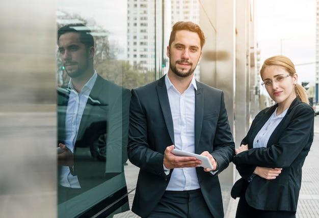 Portret młoda biznesmena i bizneswomanu pozycja blisko korporacyjnego budynku