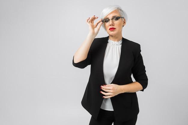 Portret młoda biznesowa dama w kostiumach odizolowywających dalej