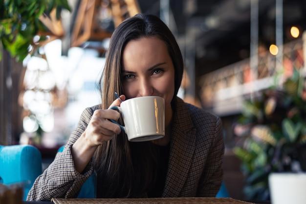 Portret młoda biznesowa kobieta pije herbaty od filiżanki zbliżenia z zamazaną restauracją