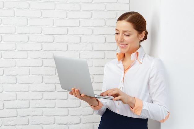 Portret młoda biznesowa kobieta używa laptop przy biurem