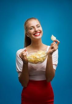 Portret młoda blond kobieta je chipsy i trzyma szklanego puchar