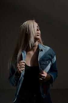Portret młoda blond kobieta na zmrok ścianie