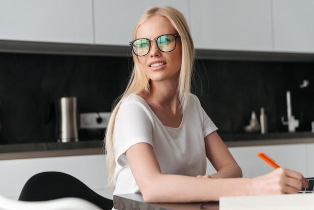 Portret młoda blondynki kobieta pracuje w domu