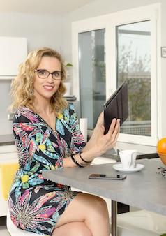 Portret młoda blondynki kobieta w kuchni z pastylka komputerem