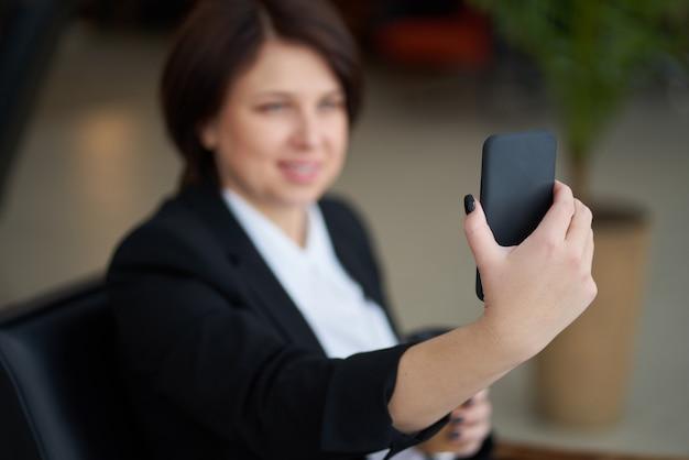 Portret młoda caucasian biznesowa kobieta jest ubranym czarnego kostium robi selfie na telefonie podczas gdy kawowa przerwa