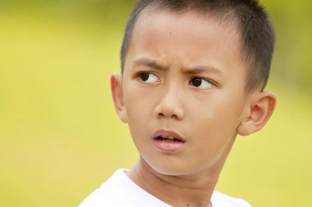 Portret młoda chłopiec w zieleni polu