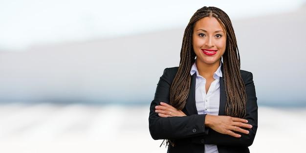 Portret młoda czarna biznesowa kobieta krzyżuje jego ręki, uśmiechnięty i szczęśliwy, być ufny i życzliwy