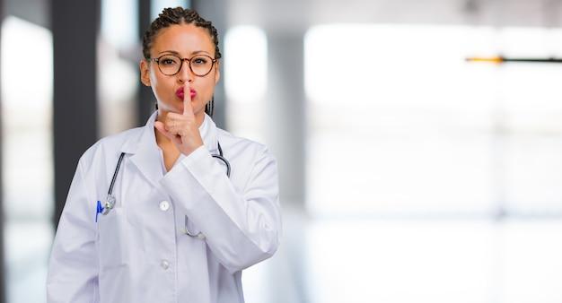 Portret młoda czarna doktorska kobieta utrzymuje sekret lub pytać dla ciszy