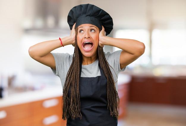 Portret młoda czarna piekarz kobieta sfrustowana i desperacka, gniewna i smutna z rękami na głowie