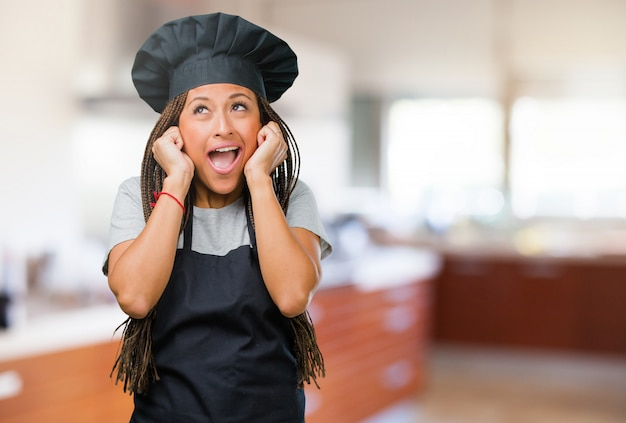 Portret młoda czarna piekarz kobieta zakrywa ucho z rękami